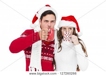 Happy couple with santa hats drinking a hot beverage on white background