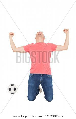 Excited man shouting with fist up and a soccer ball on white background