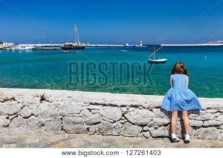 Back view of little girl enjoying views of Mediterranean sea on Mykonos island, Greece