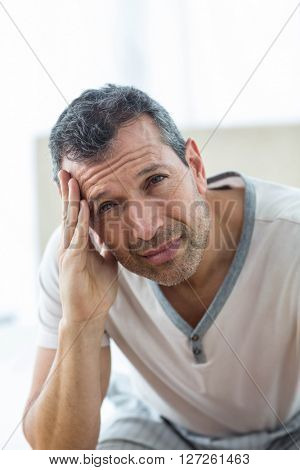 Worried man sitting on bed with hand on forehead