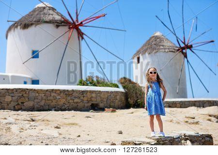 Cute little girl in front of windmills at popular tourist area on Mykonos island, Greece