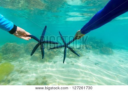 Underwater photo of couple holding blue star fish at tropical coral reef