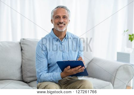 Portrait of doctor sitting with a clipboard on sofa