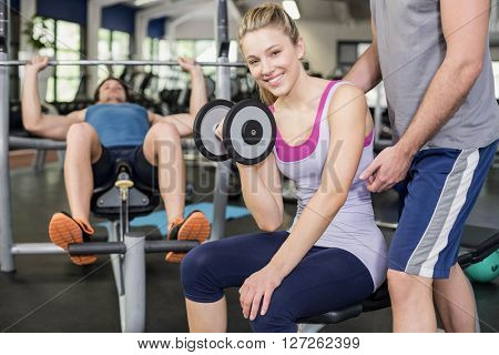 Trainer man helping woman lifting dumbbell at gym