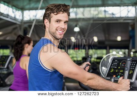 Fit man on elliptical bike at gym
