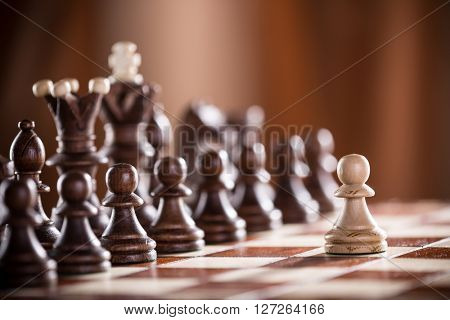 One pawn staying against full set of chess pieces, close-up.