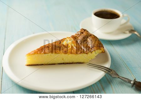 Piece of cake on a white plate on over blue