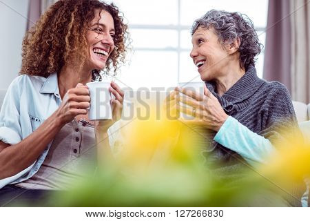 Smiling mother and daughter holding coffee mugs while discussing at home