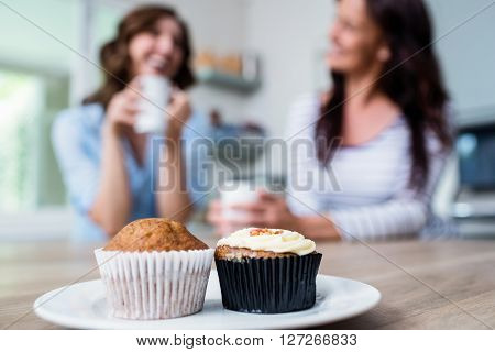 Muffins and cupcake served on table with friends sitting in background at home