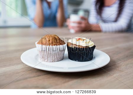 Muffin and cupcake served in plate on table with friends sitting in background at home