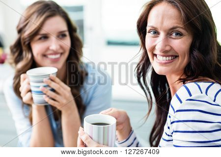 Cheerful female friends holding coffee mugs while sitting at table in kitchen