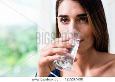 Young woman drinking water at home