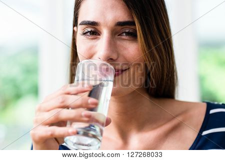 Portrait of smiling young woman drinking water at home