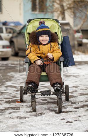 Little boy sitting in stroller in winter park