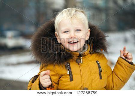 Close up portrait, little baby blonde boy in a winter park