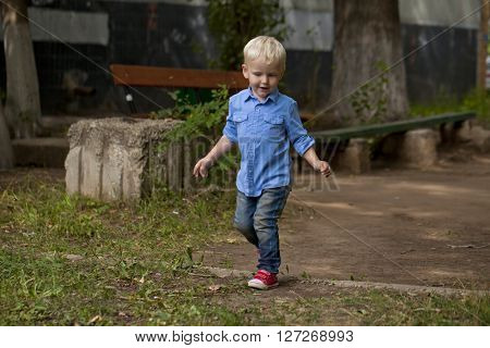 Portrait of blonde baby boy in summer street, outdoors