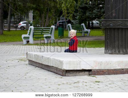 Portrait of baby boy in autumn street park