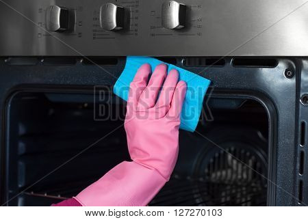close up of woman hand in protective glove with rag cleaning oven. People housework and housekeeping concept. Cleaning oven