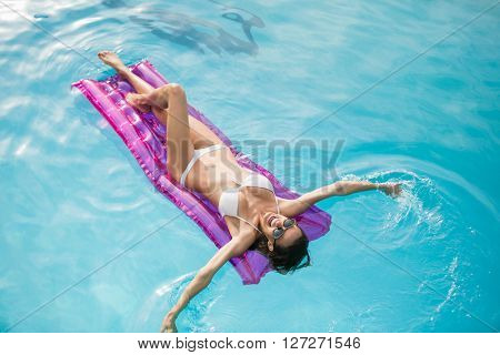 Happy young woman swimming with inflatable raft at pool