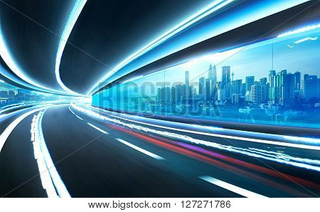 Abstract blurred speed motion road in glass tunnel over the citywith light trail