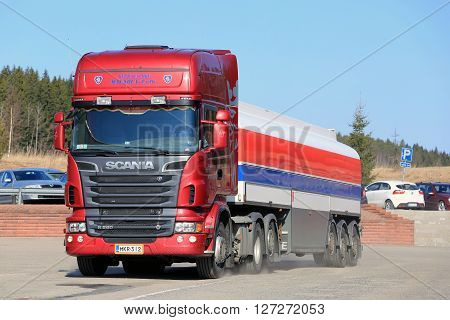 SALO, FINLAND - APRIL 16, 2016: Unnamed truck driver parks Red Scania R580 Semi tank truck at a truck stops in South of Finland on a sunny day with blue sky.