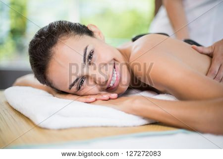 Close-up portrait of woman smiling while receiving stone massage at health spa