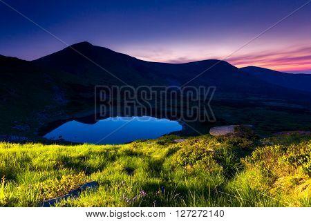 Majestic view of alpine lake illuminated lantern at twilight. Dramatic and picturesque scene. Location place National park Chornogora, Nesamovyte lake. Carpathian, Ukraine, Europe. Beauty world.