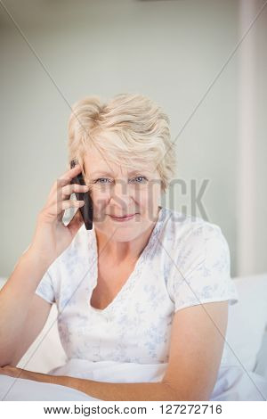 Portrait of senior woman talking on phone in bed at home