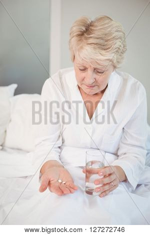 Senior woman taking medicine in bedroom at home