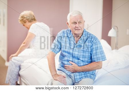 Tensed senior man and woman sitting on bed at home