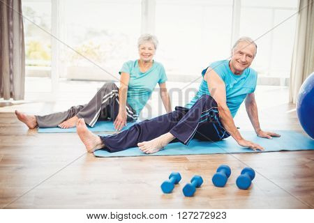 Portrait of smiling senior couple performing yoga at home