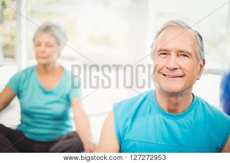 Close-up portrait of senior man smiling with wife meditating at home