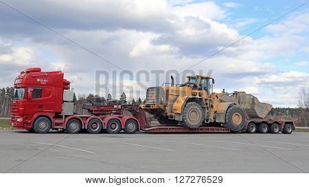 FORSSA, FINLAND - APRIL 23, 2016: Scania 164G truck stops at Forssa truck stop during the oversized transport of heavy Volvo L350F wheel loader side view.