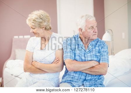 Serious senior couple looking away while sitting on bed at home