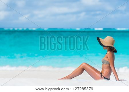 Bikini woman beach vacation sun tanning relaxing on beach. Suntan concept. Unrecognizable female adult enjoying the sunshine with straw hat sunbathing under the tropical sun on Caribbean vacation. poster