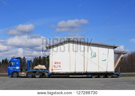 FORSSA, FINLAND - APRIL 23, 2016: Blue Volvo FH semi truck is to transport a prefabricated house module as oversize load in South of Finland.
