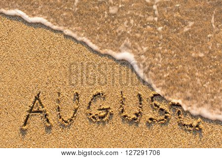 August - word drawn on the sand beach with the soft wave. Months series of 12 pictures.