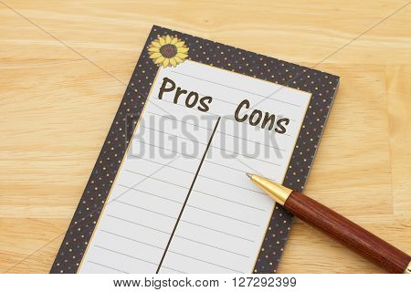 Listing your pros and cons A notepad and pen on wood background with text Pros and Cons with copy-space