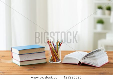 education, school, drawing, creativity and object concept - close up of crayons or color pencils and books on wooden table