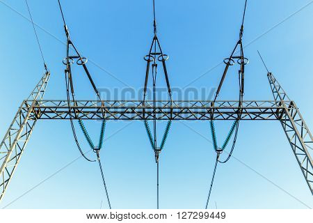 high-voltage electricity pylons against blue sky with clouds poster