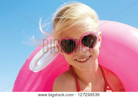little girl in swimsuit playing with an inflatable ring on the seaside.