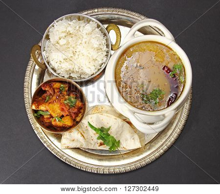 Overhead view of an Indian vegetarian meal comprising of yellow lentil daal or soup with Karahi paneer rice and chapati on a thali or plate.