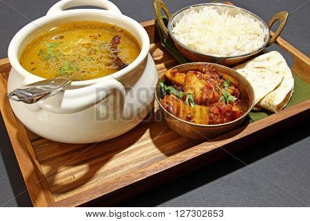 An Indian vegetarian meal comprising of yellow lentil daal or soup with Karahi paneer rice and chapati on a tray.