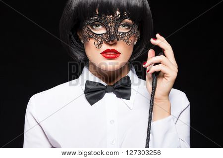 Sexy woman in wig posing with whip on black background sensuality and punishment