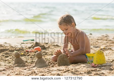 The Child Sits On The Sandy Beach Of The Reservoir And Enthusiasm Molds Of Sand Cakes
