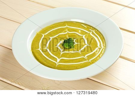 Broccoli vegetable soup cream in white plate on green and white background