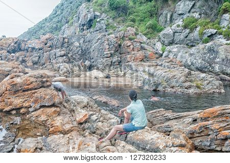 STORMS RIVER MOUTH SOUTH AFRICA - MARCH 1 2016: Unidentified tourists at the pool below the waterfall at the end of the Waterfall Trail on an overcast day. The trail follows part of the renowned Otter trail poster