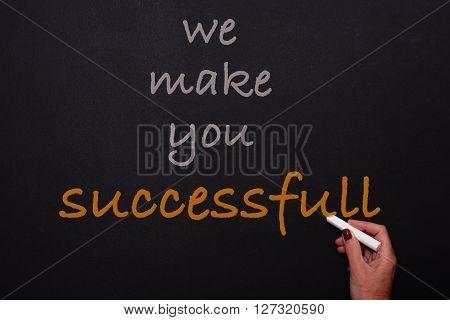 Woman writes on blackoard - we make you successfull