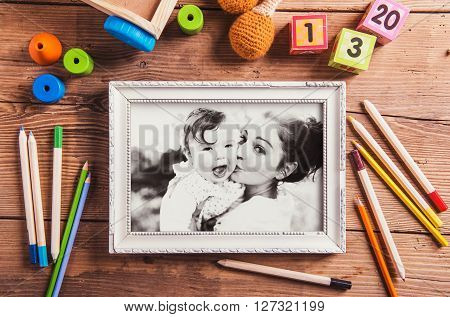 Mothers day composition. Black-and-white photo in picture frame. Various toys. Studio shot on wooden background.