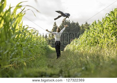 Young businessman celebrating his business freedom and success by throwing his suit jacket in the air standing in grassland between two cornfields.